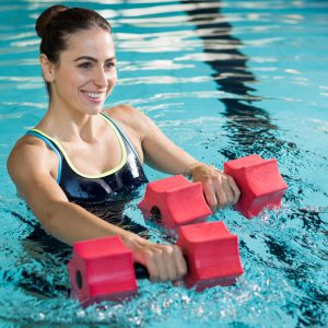 Fit woman working out with foam dumbbell in swimming pool at leisure center. Woman engaged in doing aqua aerobics in water. Young beautiful woman doing aqua gym exercise with water dumbbell in swimming pool.